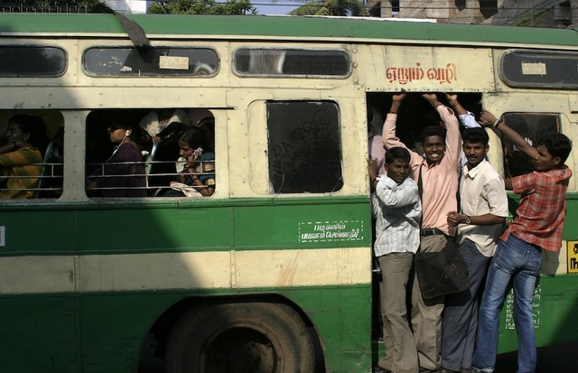 A densely packed bus in Chennai with some people even hanging onto the doorway