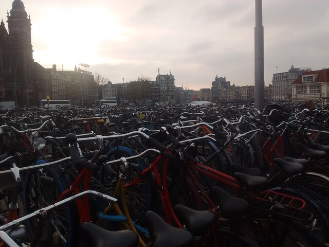 A public bicycle parking space with perhaps hundreds of parked bicycles in the foreground and Amsterdam cityscape in the background