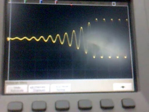 An exponentially increasing and eventually stabilizing sine wave shown on an oscilloscope