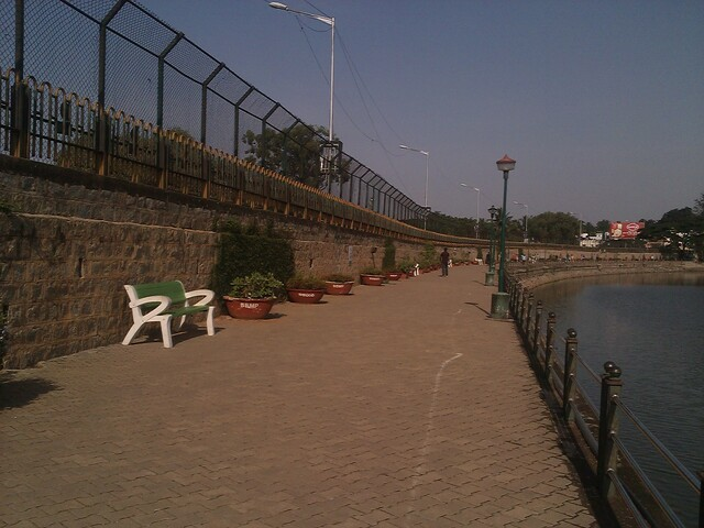 A paved path bounded by a wall on the left and a reservoir on the right